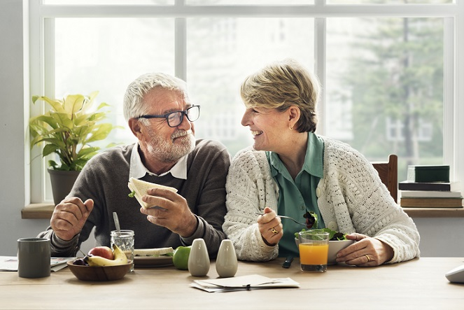 older man and woman eating healthy and smiling