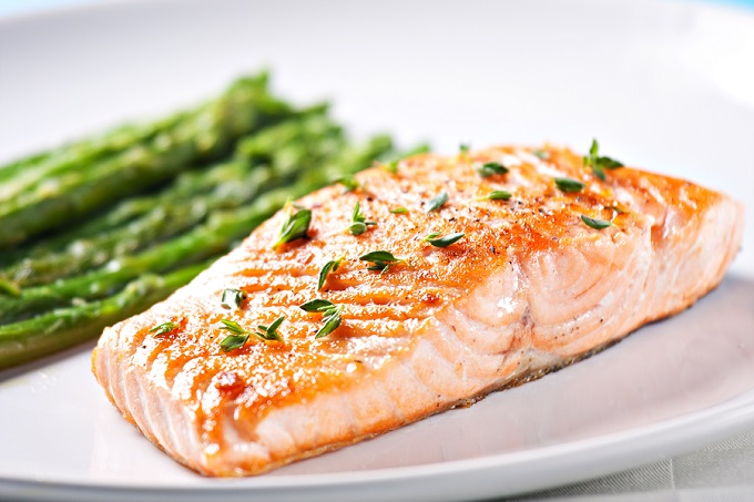 Baked salmon serving on a plate with asparagus as a side