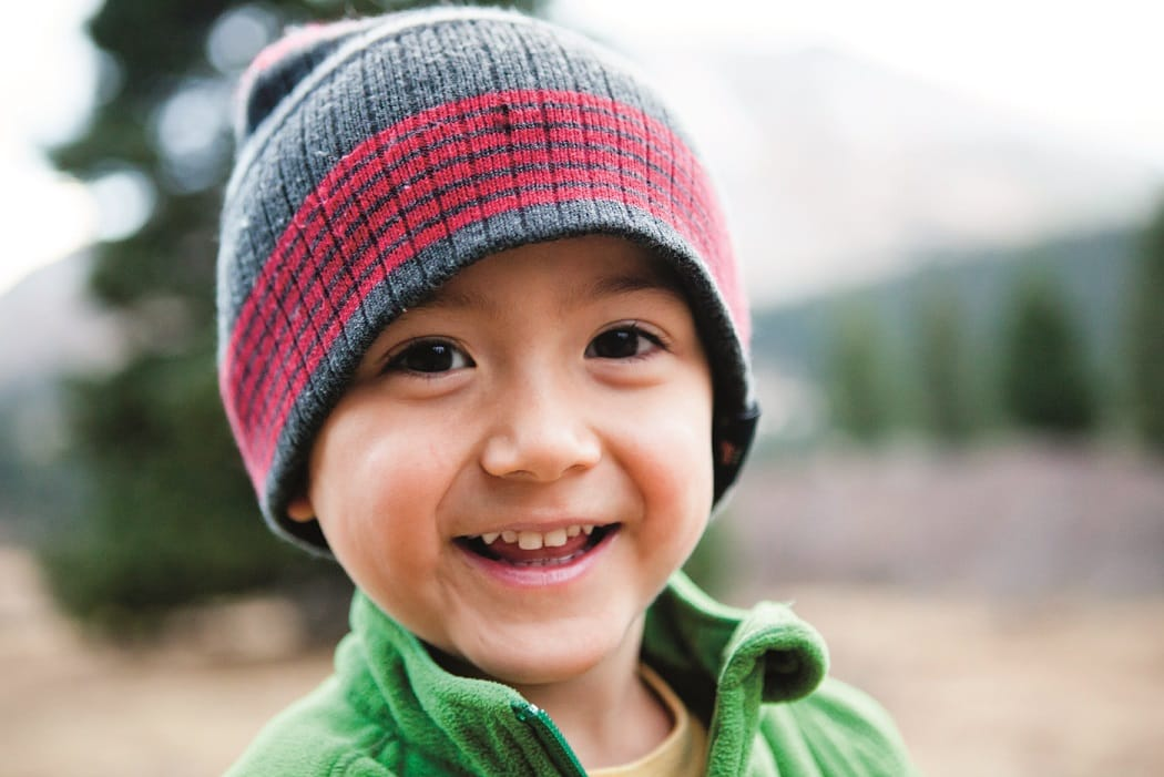 A Japanese-American boy smiles while camping in an alpine environment campground.